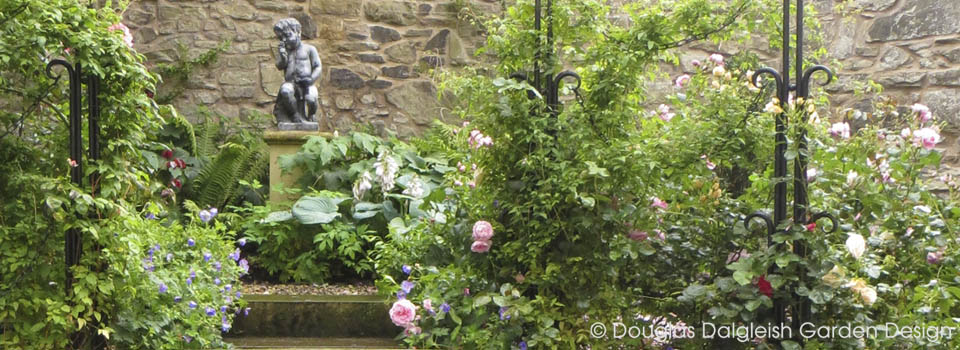 view of garden showing roses, ironwork, and sculpture on plinth in front of old stone wall