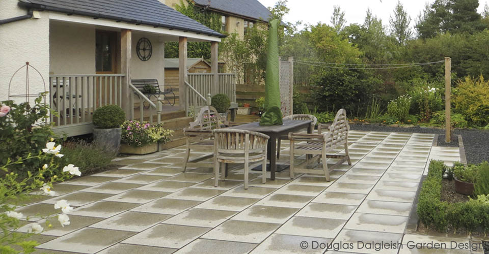 paved patio with table, chairs, benches